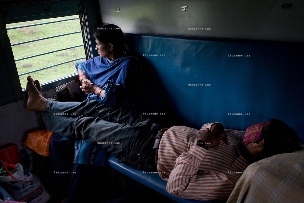 Train passengers on the Himsagar Express 6318 enjoy the passing rain and greenery in the states of Madhya Pradesh and Maharashtra on 8th July 2009.. .6318 / Himsagar Express, India's longest single train journey, spanning 3720 kms, going from the mountains (Hima) to the seas (Sagar), from Jammu and Kashmir state of the Indian Himalayas to Kanyakumari, which is the southern most tip of India...Photo by Suzanne Lee / for The National