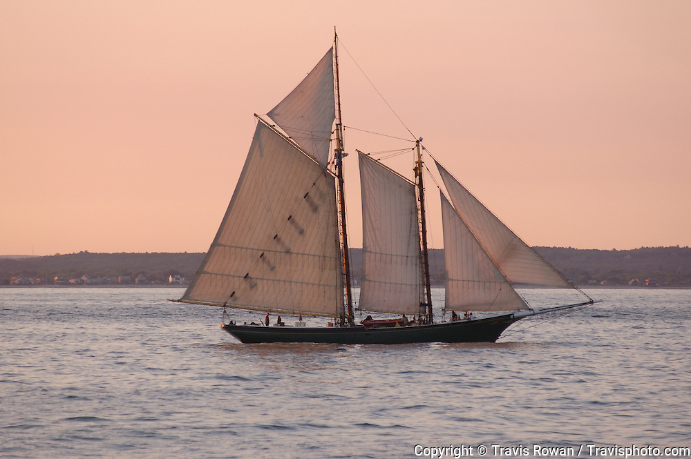A classic sailing yacht cruises along the New England coast.