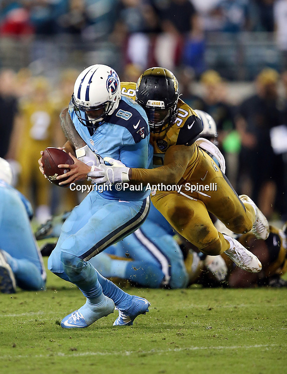 Tennessee Titans quarterback Marcus Mariota (8) gets sacked on the last play of the game, with five seconds on the clock and no time outs, by Jacksonville Jaguars defensive end Andre Branch (90) during the 2015 week 11 regular season NFL football game against the Jacksonville Jaguars on Thursday, Nov. 19, 2015 in Jacksonville, Fla. The Jaguars won the game 19-13. (©Paul Anthony Spinelli)