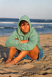 Good looking man in a hooded sweatshirt sitting on the beach