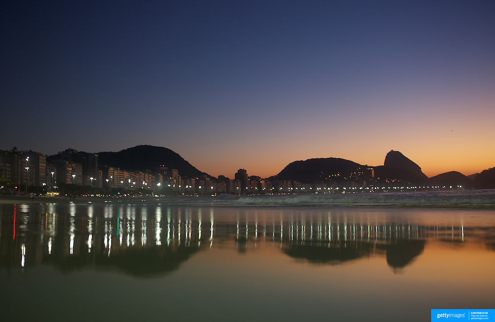 Sunrise at Rio de Janeiro's most famous beach Copacabana with Sugar Loaf mountain in the distance. Rio de Janeiro, Brazil. 21st July 2010. Photo Tim Clayton..