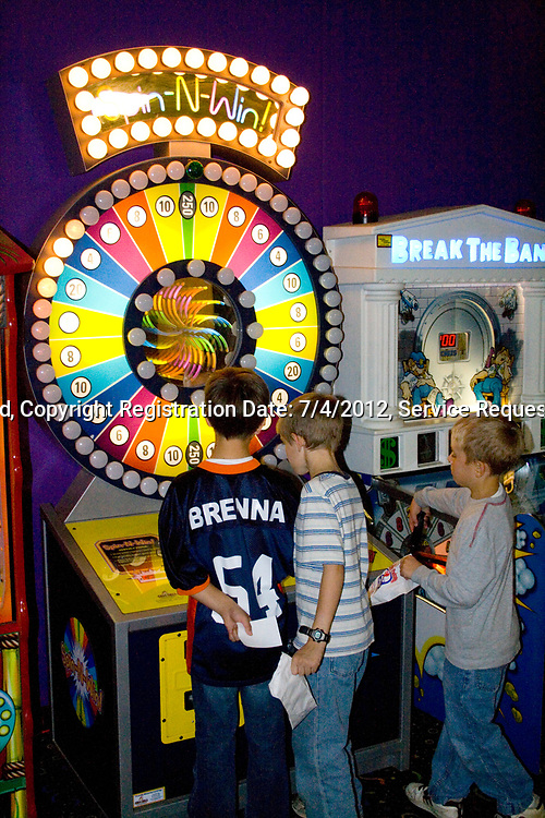 Boys age 7 playing Spin-N-Win electronic video arcade game. Grand Slam Amusement Center Burnsville Minnesota MN USA