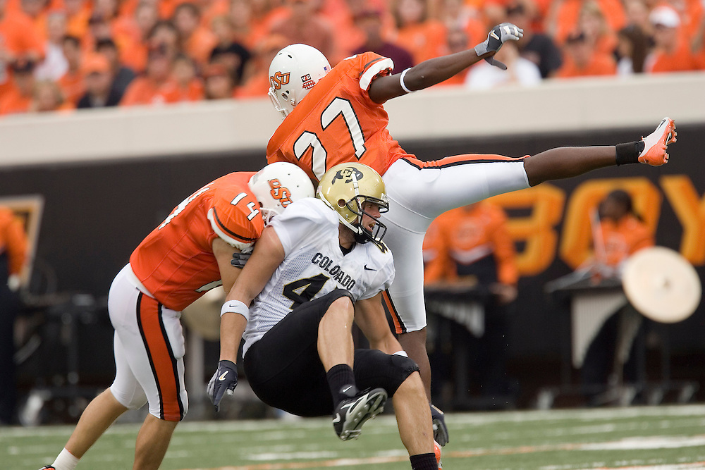 Oklahoma State Cowboys defensive backs Chase Holland and Calvin Mickens hit Colorado Buffaloes running back Brendan Schaub while attempting to catch a pass during a 34 to 0 loss to the Colorado Buffaloes on October 1, 2005 at Boone Pickens Stadium in Stillwater, Oklahoma.