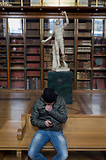 A visitor uses his phone instead of admiring the sculpture of Rondanini's Faun - a 2nd century Roman copy of a Greek original - in the Enlightenment Gallery of the British Museum, on 11th April 2018, in London, England.