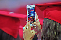 Student takes a photo at commencement.