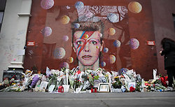 © Licensed to London News Pictures. 10/01/2017. London, UK. A fan (R) reads messages written on a mural and shrine to David Bowie in Brixton. David Bowie who died a year ago today, was born in Brixton, south London. Photo credit: Peter Macdiarmid/LNP