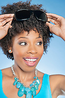 Cheerful African American woman adjusting sunglasses over colored background