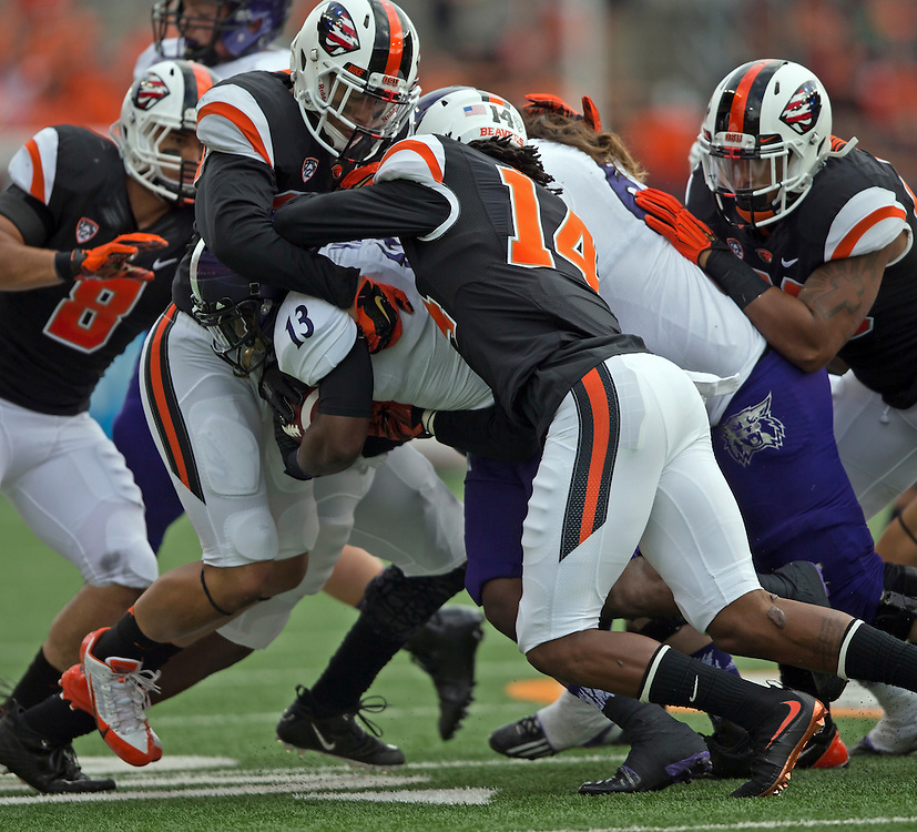 Weber State runningback Eric Wilkes (13) is swarmed over by the Oregon State defense during the Beavers' 26-7 victory in the 2015 season opener in Reser Stadium, in Corvallis, on Friday, Sept. 4, 2015.