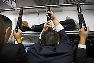 Man sover stående på tunnelbanan, Tokyo, Japan