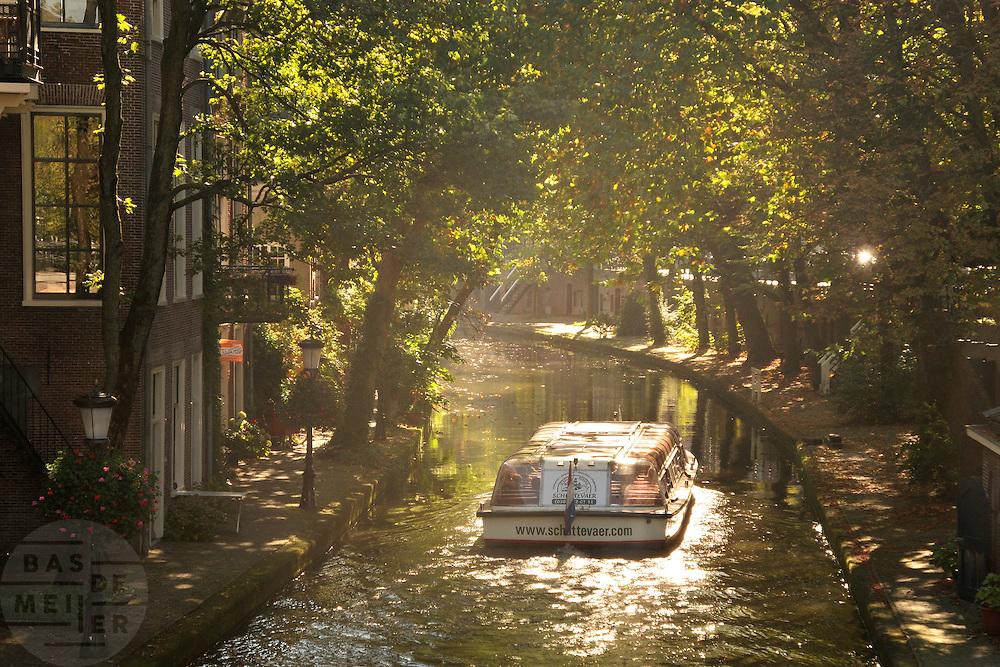 Een rondvaartboot vaart over de Oudegracht in Utrecht.<br /> <br /> A boat trip boat is cruising over the canals in Utrecht