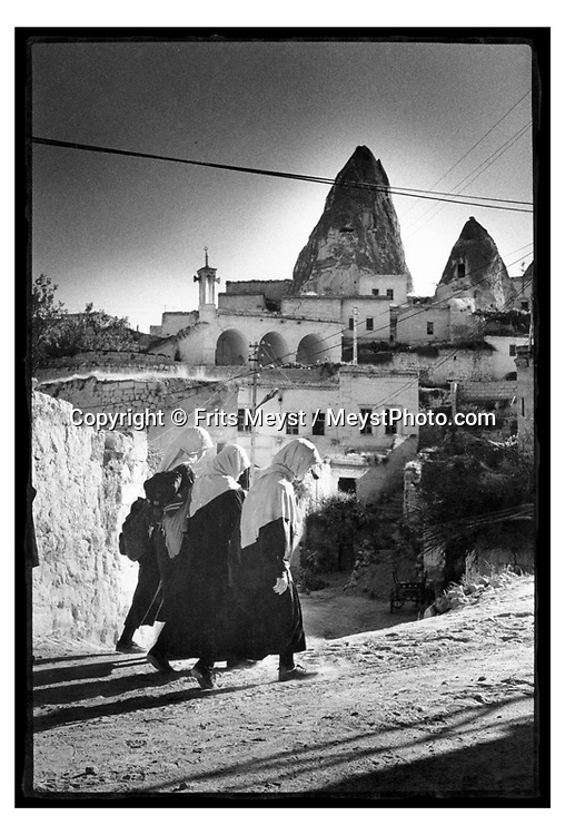 GOREME, CAPPADOCIA, TURKEY, 2000.  Women offload their horse cart in fromt of their cave house in the rock. Traditional life in Cappadocia has come under heavy strain, due to the increased tourism. the young generation is not interested in working the fields if they can work in a carpetshop, restaurant or bar. Therefore centuries old skills and habits will die with the elderly. Cappadocia is knowns for its landscape with conical shaped rock formations and cave dwellings in which the local people live. ©Photo by Frits Meyst/Adventure4ever.com
