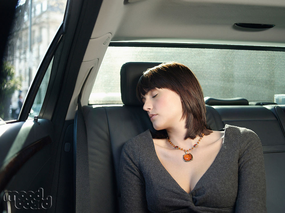 Mid adult woman sleeping at back seat of car