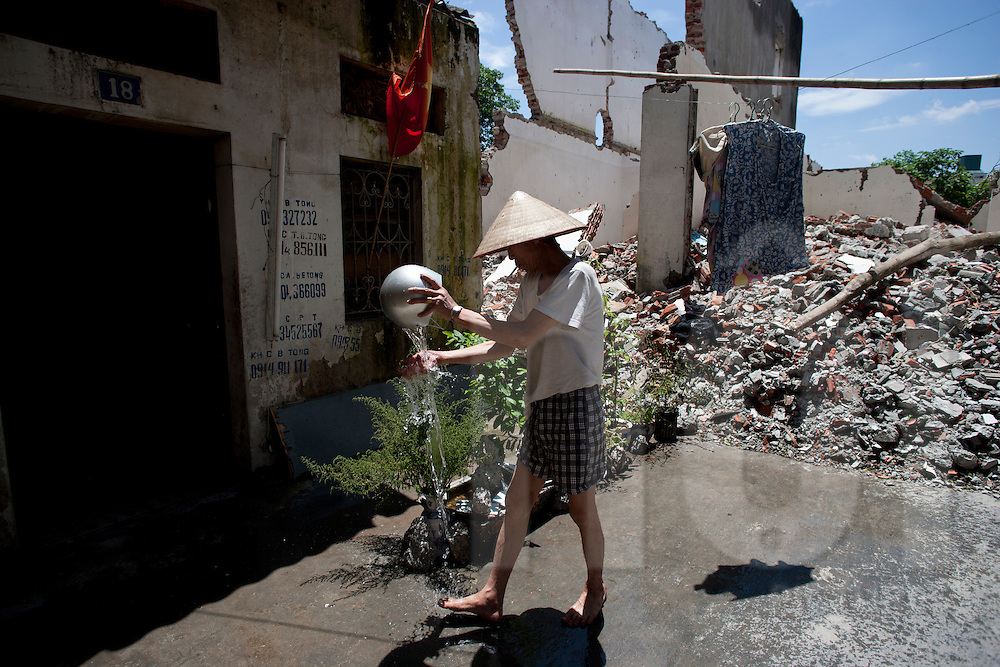 An old man wearing a conical hat watering plants next to building rubble on Hoang Hoa Tham street, Hanoi, Vietnam, Southeast Asia
