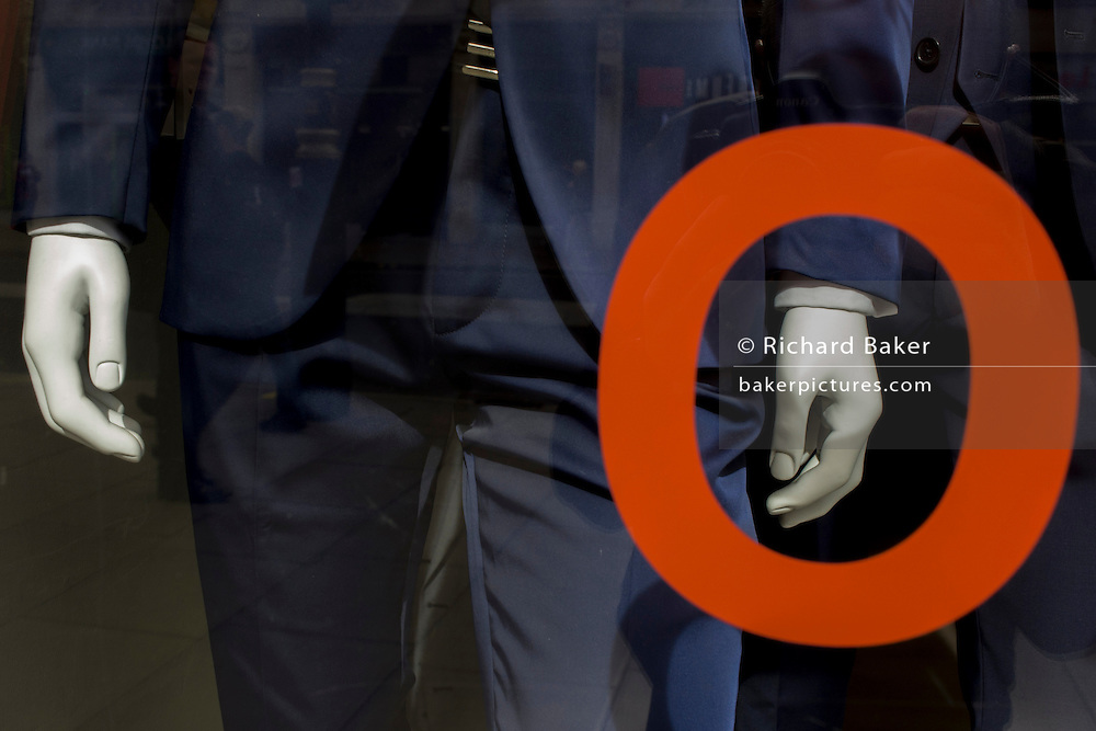 Trendy blue suits with red prices and lettering on display in a central London menswear shop.