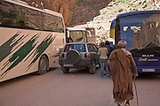Old man confronted by traffi congestion of tourist coach buses, Todra gorge, Morocco,