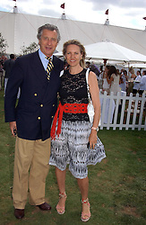 ARNAUD BAMBERGER and his wife CARLA at the Cartier International polo at Guards Polo Club, Windsor Great Park, on 30th July 2006.<br />
