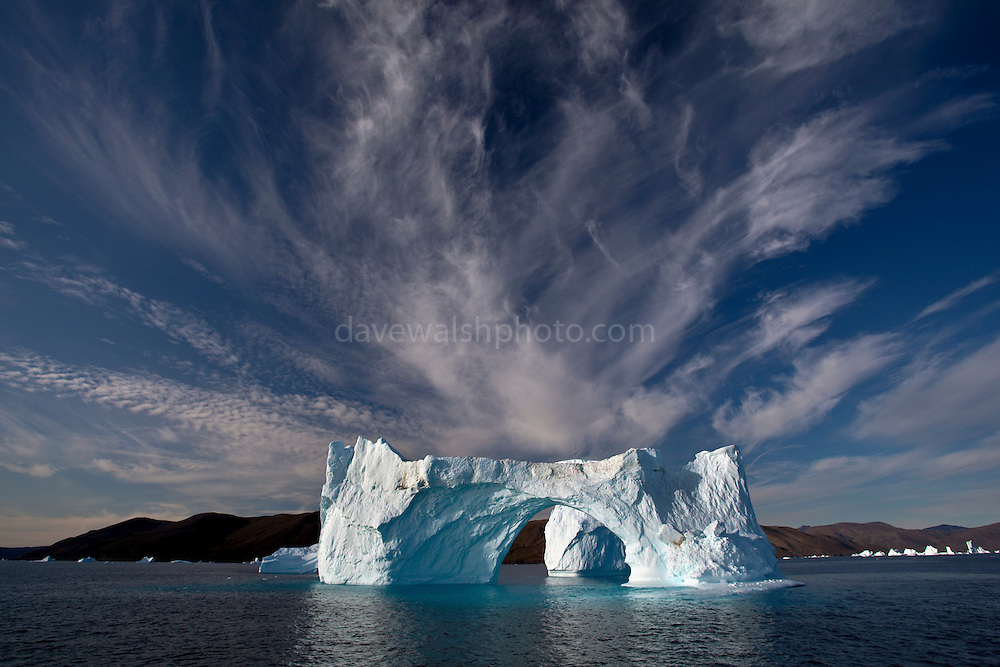 Iceberg: Cirrus clouds over an arched Iceberg near Nuugaatsiaq, Baffin Bay, West Greenland.