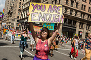"""New York, NY - 25 June 2017. New York City Heritage of Pride March filled Fifth Avenue for hours with groups from the LGBT community and it's supporters. A woman from the Ragtag Theater, an LGBT theater group for families, with a sign that reads """"You are enough."""""""