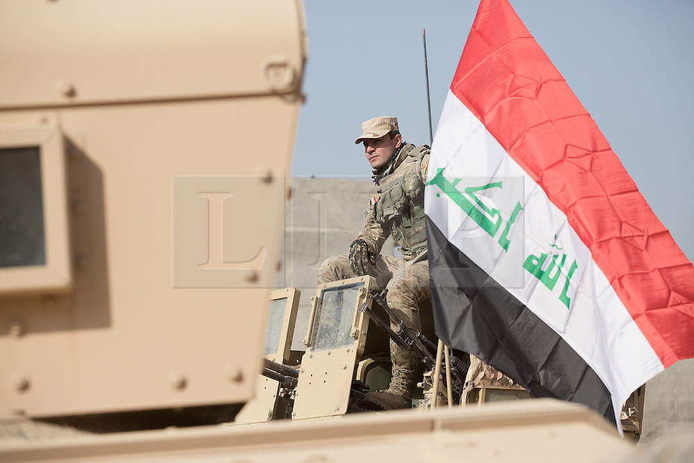 Licensed to London News Pictures. 11/11/2016. Mosul, Iraq. A soldier, belonging to the Iraqi Army's 9th Armoured Division, sits on the turret of an armoured Humvee as his unit visits Mosul's Al Inisar district on the south east of the city. The Al Intisar district was taken four days ago by Iraqi Security Forces (ISF) and, despite its proximity to ongoing fighting between ISF and ISIS militants, many residents still live in the settlement without regular power and water and with dwindling food supplies.<br /> <br /> The battle to retake Mosul, which fell June 2014, started on the 16th of October 2016 with Iraqi Security Forces eventually reaching the city on the 1st of November. Since then elements of the Iraq Army and Police have succeeded in pushing into the city and retaking several neighbourhoods allowing civilians living there to be evacuated - though many more remain trapped within Mosul.  Photo credit: Matt Cetti-Roberts/LNP