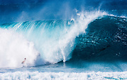 A surfer straightening out and getting blasted by the whitewater at the Banzai Pipeline, North Shore, Oahu, Hawaii