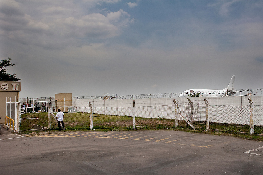Deported men and women arriving on a US government chartered plane wait for processing in San Salvador. Many of the deportees left El Salvador when they were children and suffer severe culture shock when they return. Deported gang members usually link up with local affiliates becasue there family ties are weak.  The international nature of the 18th street and MS-13 gangs, make it exceedingly difficult for authorities to control.  And it is the social divisions and fractures caused by immigration that precisely push youth to start and join gangs.