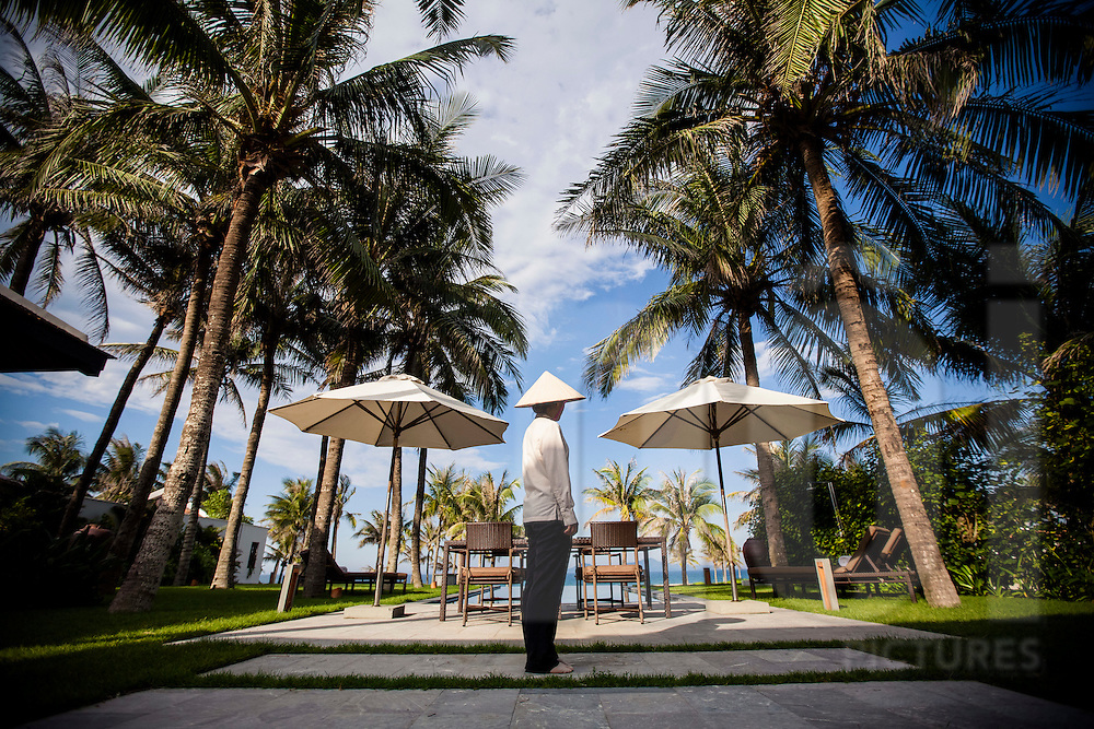 A Vietnamese staff stands in the yard of a private villa at the Nam Hai resort, Hoi An, Vietnam, Southeast Asia