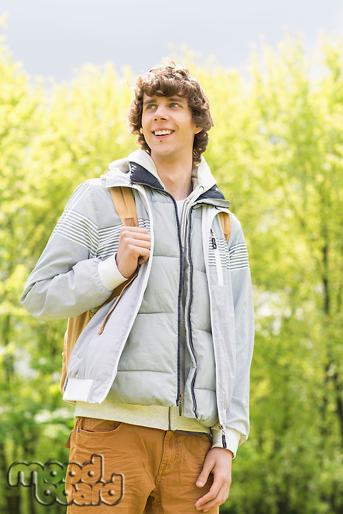 Young man with backpack standing at college campus