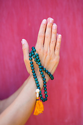 Woman Hands in Prayer Position Holding Beads