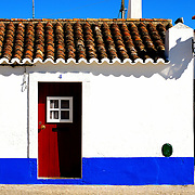 A woman walking by a traditional house in Porto Covo seaside village, Portugal.