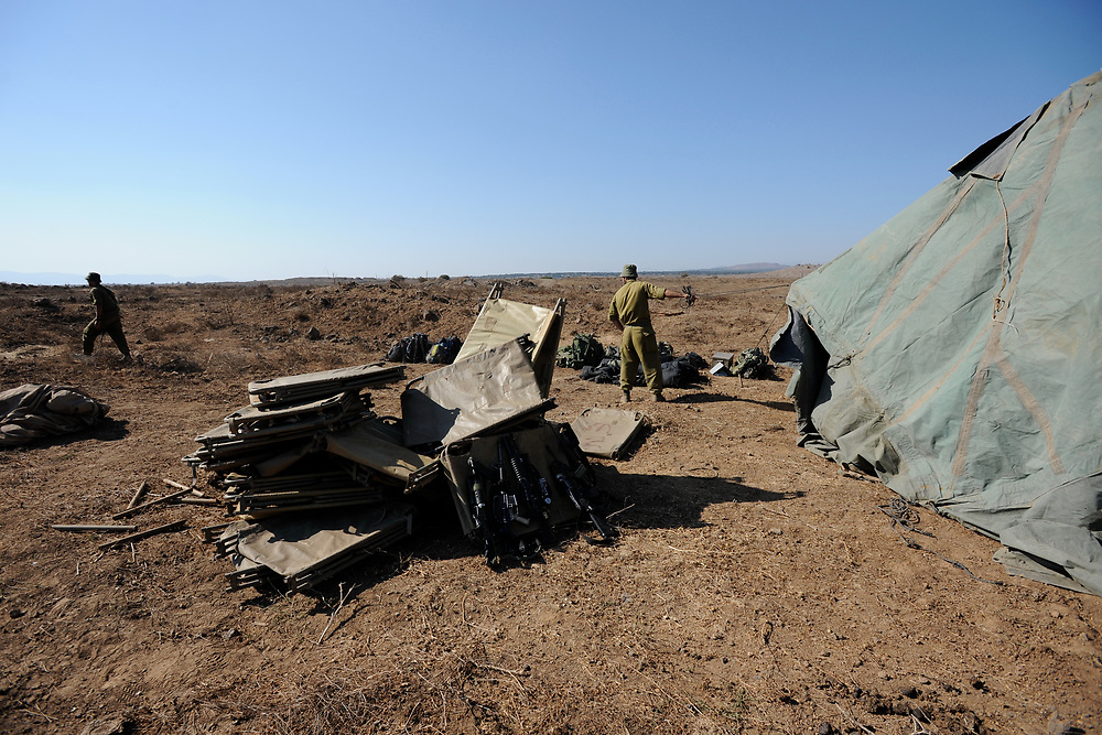 GOLAN HEIGHTS, UNSPECIFIED - AUGUST 30: Field beds and personal guns are piled on the ground as Israeli soldiers construct a military field camp on August 30, 2013 near the border with Syria, in the Israeli-annexed Golan Heights. Tensions is rising in Israel amid talks of a military intervention In Syria. Photo by Gili Yaari