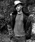 Young man posing in hat and open jacket.