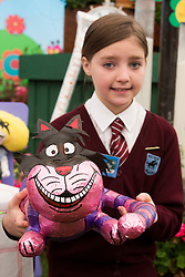 © Licensed to London News Pictures. 19/05/2014. London, England. Freya, 10, from the Holtspur School near Beaconsfield the Cheshire Cat which their school designed for the Miracle Gro'wers Discovery and Learning Garden.  Press Day at the RHS Chelsea Flower Show. On Tuesday, 20 May 2014 the flower show will open its doors to the public.  Photo credit: Bettina Strenske/LNP