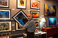 "Photographer Wayne Eastep installing prints for the collection ""The Living Seas"" at Eastep Photography Gallery.<br />