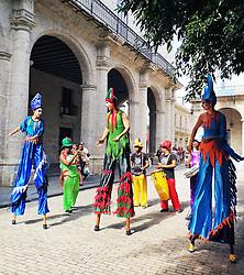 Colorful stiltwalkers dancing in Old Havana street.
