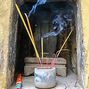 Sticks of incense burn in a small shrine at Tran Quoc Pagoda on a small island on West Lake (Ho Tay). Originally built in the 6th century on the banks of the Red River, a changing course of the river forced the pagoda to be relocated in 1615 to Golden Fish (Kim Ngu) islet on the lake.
