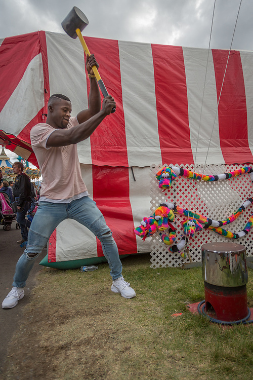 """U.S. Army Private Reuben Geimah test his strength at the """"High Striker"""" on the midway at the Alaska State Fair in Palmer, Alaska"""