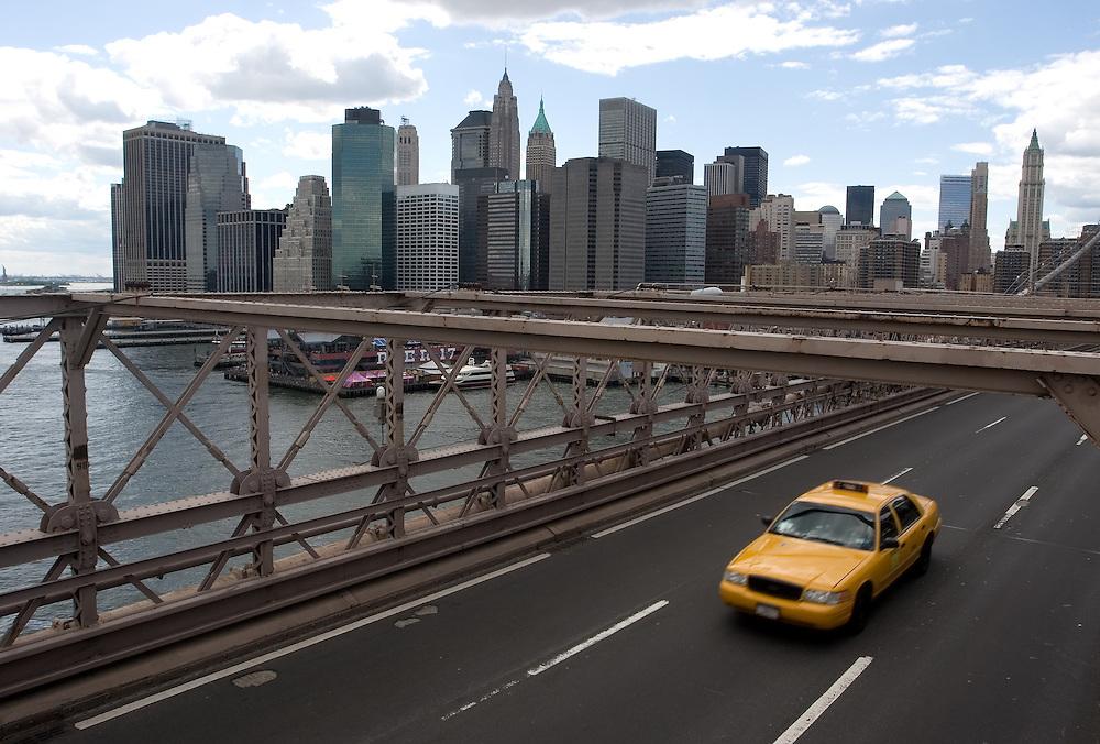 """Un """"yellow cab"""" (taxi amarillo) de Nueva York cruza el puente de Brooklyn con Manhattan al fondo."""
