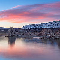 Rising sun illuminates beautiful clouds above the mountains adjacent Mono Lake tufas. Lee Vining, California