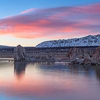 Rising sun illuminates beautiful clouds above the mountains adjacent Mono Lake tufas. Lee Vining, California