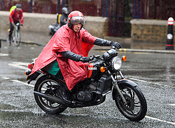 © London News Pictures. 20/06/2016. London, UK. A man on a motorbike keeps himself dry underneath a poncho during heavy rain in central London on the day of Summer Solstice, the longest day of the year. Photo credit: Ben Cawthra/LNP
