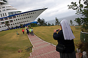 The nun photographing the group of handicapped people by visiting Suncruise resort, the giant cruise ship in the background / Jeongdongjin, South Korea, Republic of Korea, KOR, 07 October 2009.