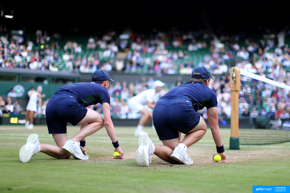 LONDON, ENGLAND - JULY 14: Ball Boys crouch near the net ready to retrieve the ball on Center Court during the Wimbledon Lawn Tennis Championships at the All England Lawn Tennis and Croquet Club at Wimbledon on July 14, 2017 in London, England. (Photo by Tim Clayton/Corbis via Getty Images)
