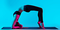 one caucasian woman exercising Chakrasana  yoga exercices  in silhouette studio isolated on blue background