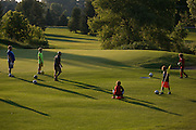 Players convene on the green area during a round of foot golf at Victor Hills Golf Club in Victor on Monday, July 27, 2015. The game is played on golf courses, and requires players to kick a soccer ball into a large hole.