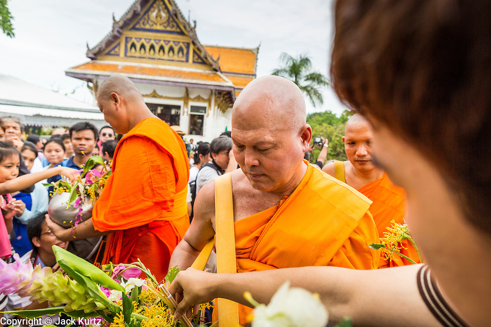 "22 JULY 2013 - PHRA PHUTTHABAT, THAILAND: Buddhist monks receive flowers from people near the Mondop (chapel that houses the footprint) before the Tak Bat Dok Mai at Wat Phra Phutthabat in Saraburi province of Thailand, Monday, July 22. Wat Phra Phutthabat is famous for the way it marks the beginning of Vassa, the three-month annual retreat observed by Theravada monks and nuns. The temple is highly revered in Thailand because it houses a footstep of the Buddha. On the first day of Vassa (or Buddhist Lent) people come to the temple to ""make merit"" and present the monks there with dancing lady ginger flowers, which only bloom in the weeks leading up Vassa. They also present monks with candles and wash their feet. During Vassa, monks and nuns remain inside monasteries and temple grounds, devoting their time to intensive meditation and study. Laypeople support the monastic sangha by bringing food, candles and other offerings to temples. Laypeople also often observe Vassa by giving up something, such as smoking or eating meat. For this reason, westerners sometimes call Vassa the ""Buddhist Lent.""     PHOTO BY JACK KURTZ"