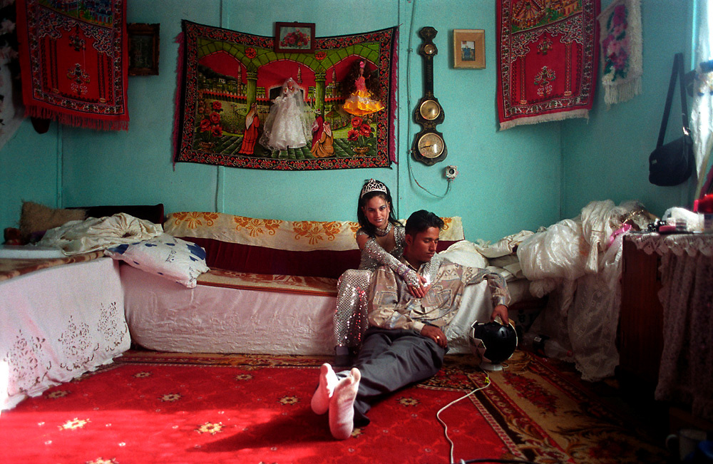 Bekim Gusani and his young wife pose for a wedding photo. They are ethnic Roma (gypsy) and live in an internal refugee camp in kosovo. Bekim couldn't afford the brides price, so she ran away to be with him. According to tradition they are not welcome at her family until he pays. He has several jobs, and hopes to start paying soon. There used to be a large roma area in Mitrovica, but now the inhabitants are spread in refugee camps in Serbia, Montenegro, Kosovo and Macedonia. .