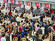 "24 DECEMBER 2015 - BANGKOK, THAILAND: Passengers line up at the Air Asia counters in the new domestic terminal at Don Muang (also spelled Don Mueang) International Airport. The new terminal had its ""soft"" opening Dec. 24. Don Muang is the airport used by low cost airlines serving Bangkok and is now the largest airport in the world for low cost carriers. In 2014, more than 21million passengers used Don Muang. Don Muang International Airport is the oldest airport in Asia and one of the oldest airports in the world. It started functioning as an airfield in 1914.     PHOTO BY JACK KURTZ"