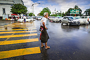 12 JUNE 2013 - YANGON, MYANMAR:     A man crosses Strand Rd near the waterfront after a rain storm in Yangon, Myanmar.     PHOTO BY JACK KURTZ