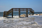 Remnants of backyard deck stands in open water on Ocean Isle Beach, NC where the ocean has reclaimed land, homes and a large section of 2nd Street due to rising tides and erosion. About 3,800 homes are packed together on the narrow seven-mile long Ocean Isle. The rising ocean has worn away at the eastern end, where streets and lots have been steadily disappearing.