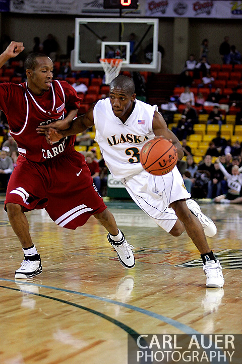 24 November 2005:  University of Alaska Anchorage senior guard Kemmy Burgess drives past USC's Tarence Kinsey in the UAA Seawolves 60-65 loss to the South Carolina Gamecock's in the first round of the Great Alaska Shootout at the Sullivan Arena in Anchorage Alaska.